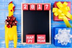Brinque a galinha amarela, a caixa de presente atual, o quadro-negro e y novo feliz Fotografia de Stock Royalty Free