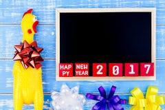 Brinque a galinha, o quadro-negro e o número amarelos do ano novo feliz 2017 sobre Imagens de Stock