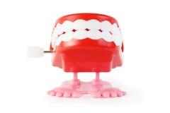 Brinque a maxila do maquinismo de relojoaria com os dentes brancos nos pés cor-de-rosa Fotografia de Stock Royalty Free