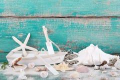 Brinque o barco com estrela do mar e as conchas do mar com um CCB de madeira de turquesa fotografia de stock royalty free