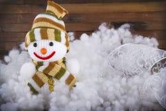 Brinque o boneco de neve na neve no fundo de madeira Imagens de Stock