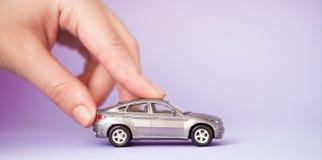 Brinque o carro da criança na mão do ` s da mulher Curso do crédito bancário do seguro da compra aonde ir conceito da viagem da v fotografia de stock