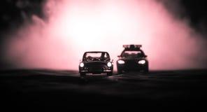 Brinque o carro de polícia de BMW que persegue um carro de Ford Thunderbird na noite com fundo da névoa Cena da decoração do brin Fotografia de Stock