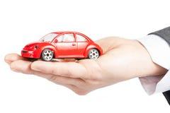 Brinque o carro na mão do conceito do homem de negócio para o seguro, a compra, o aluguer, o combustível ou o serviço e os custos  Imagem de Stock Royalty Free