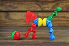 Brinque o cavalo e a bola feitos dos detalhes coloridos plásticos Imagem de Stock