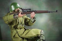 Brinque o fundo verde de seda realístico diminuto do boneco de ação do soldado do homem Foto de Stock Royalty Free