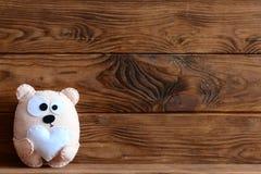 Brinquedo adorável do urso de feltro com coração Brinquedo do urso de peluche no fundo de madeira marrom com lugar vazio para o t Fotos de Stock