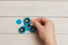 Brinquedo azul do alívio de esforço do girador da inquietação no fundo de madeira Imagem de Stock Royalty Free