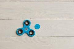 Brinquedo azul do alívio de esforço do girador da inquietação no fundo de madeira Imagem de Stock