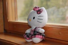 Brinquedo bonito de Hello Kitty no fundo da janela imagens de stock royalty free