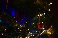 Brinquedo da árvore de Natal da quebra-nozes com bola e as lanternas elétricas douradas Fotografia de Stock