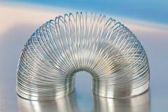 Brinquedo de aço da mola no fundo metálico azul Fotografia de Stock Royalty Free