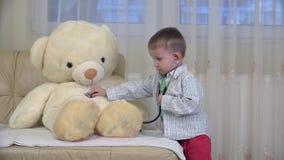 Brinquedo de consulta do urso de peluche do doutor da criança pequena, beijando vídeos de arquivo