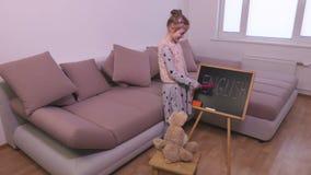 Brinquedo de ensino do coelho da menina perto do quadro-negro filme