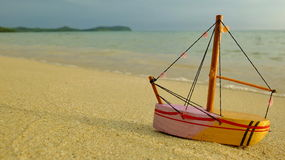 Brinquedo de madeira do barco na praia imagens de stock