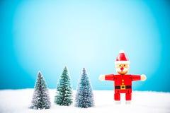 Brinquedo de madeira Santa Claus na floresta e na neve diminutas Foto de Stock Royalty Free