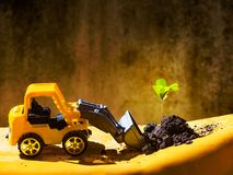 Brinquedo do caminhão do carregador da parte frontal que escava acima a planta verde e a terra sobre Fotografia de Stock Royalty Free