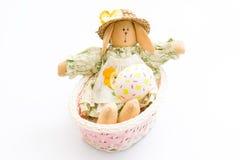 Brinquedo do coelhinho da Páscoa em uma cesta cor-de-rosa com o ovo no fundo branco Imagem de Stock
