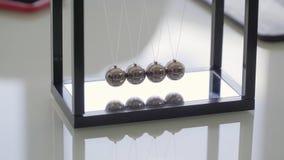 Brinquedo do escritório do berço de Newton que mostra bolas de metal de balanço no quadro preto na tabela video estoque