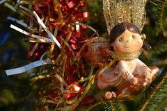 Brinquedo do ornamento do Natal como um anjo da menina que voa em uma estrela, ornating uma árvore de abeto natural em um parque imagens de stock royalty free