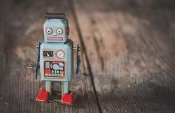 Brinquedo do robô, símbolo para um chatbot ou bot social e algoritmos Textura de madeira fotografia de stock royalty free
