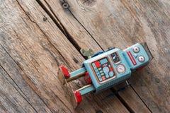 Brinquedo do robô, símbolo para um chatbot ou bot social e algoritmos Textura de madeira imagem de stock royalty free