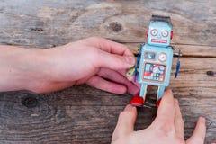 Brinquedo do robô, símbolo para um chatbot ou bot social e algoritmos Textura de madeira imagens de stock royalty free