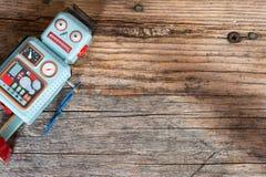 Brinquedo do robô, símbolo para um chatbot ou bot social e algoritmos Textura de madeira fotos de stock