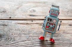 Brinquedo do robô, símbolo para um chatbot ou bot social e algoritmos Textura de madeira imagem de stock