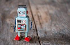 Brinquedo do robô, símbolo para um chatbot ou bot social e algoritmos Textura de madeira fotografia de stock