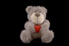 Brinquedo do urso da peluche com coração no fundo preto Fotografia de Stock Royalty Free