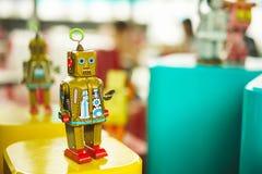 Brinquedo dourado do robô do vintage velho em um suporte Robótica e projeto do passado Imagem de Stock Royalty Free