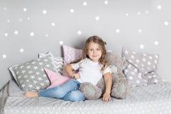 Brinquedo favorito A crian?a da menina senta-se no urso de peluche do abra?o da cama em seu quarto A crian?a prepara-se para ir p fotos de stock