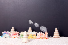 Brinquedo locomotivo coberto do trem com fumo e árvores spruce na neve Imagem de Stock Royalty Free