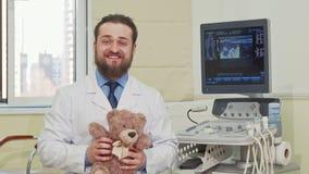 Brinquedo masculino amigável do urso de peluche da terra arrendada do pediatra, acenando à câmera filme