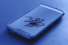 Brinquedo plástico da aranha na ação da corrida na superfície do telefone celular fotos de stock
