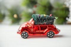 Brinquedo vermelho diminuto do carro com a árvore de abeto no foco seletivo de luz natural do fundo do Natal Imagem de Stock Royalty Free
