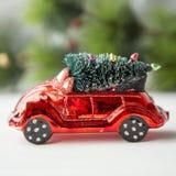 Brinquedo vermelho diminuto do carro com a árvore de abeto no quadrado do foco seletivo de luz natural do fundo do Natal Foto de Stock