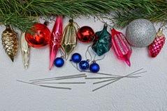 Brinquedos brilhantes novos do ` s do ano com luzes de Bengal e ramos do pinho em um fundo cinzento Foto de Stock Royalty Free