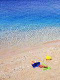 Brinquedos das crianças coloridas na areia do mar Imagem de Stock