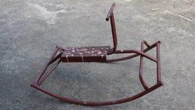 Brinquedos de aço do cavalo de balanço que balançam no assoalho concreto vídeos de arquivo