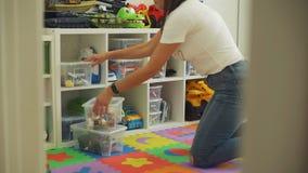 Brinquedos de organização da jovem mulher em casa filme