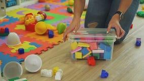 Brinquedos de organização da mulher no assoalho em casa video estoque