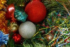 Brinquedos de vidro novos do ` s do ano em decorações brilhantes e em agulhas verdes Imagem de Stock Royalty Free