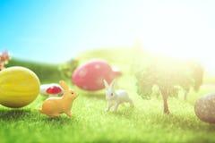 Brinquedos do coelho com ovos da páscoa em uma grama de prado Prado amarelo da mola do ovo da páscoa com dois coelho e ovos da pá foto de stock