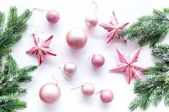 Brinquedos do Natal As estrelas e as bolas cor-de-rosa perto do pinho ramificam na opinião superior do fundo branco Fotos de Stock Royalty Free