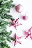 Brinquedos do Natal As estrelas e as bolas cor-de-rosa perto do pinho ramificam na opinião superior do fundo branco Fotografia de Stock