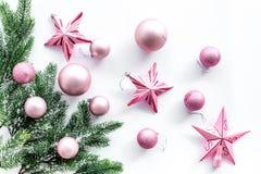 Brinquedos do Natal As estrelas e as bolas cor-de-rosa perto do pinho ramificam na opinião superior do fundo branco Imagem de Stock Royalty Free
