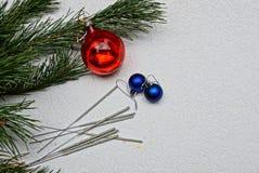 Brinquedos do ` s do ano novo e luzes de Bengal com ramos verdes Imagens de Stock