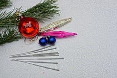 Brinquedos do ` s do ano novo e luzes de Bengal com ramos verdes Foto de Stock